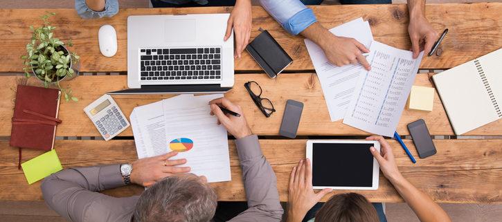 Vue du dessus d'un groupe de gens qui analysent des schémas et diagrammes sur un bureau