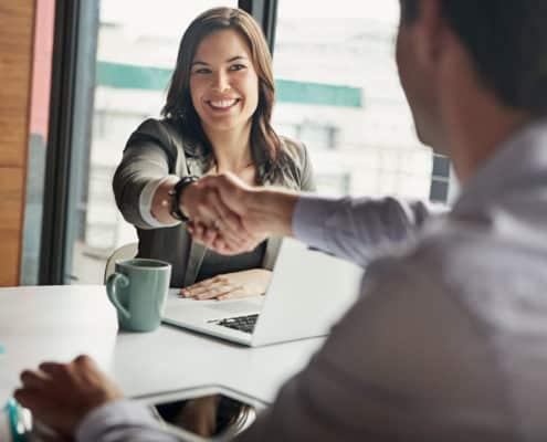 Une femme et un homme, assis à une table, se serrent la main