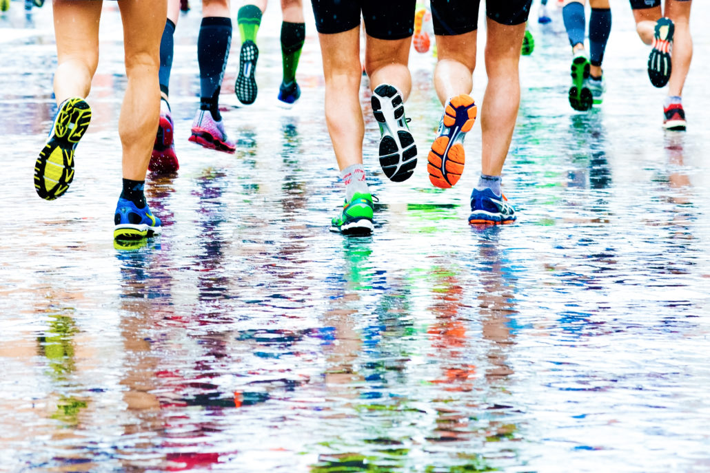 sportifs qui courent sur un sol humide